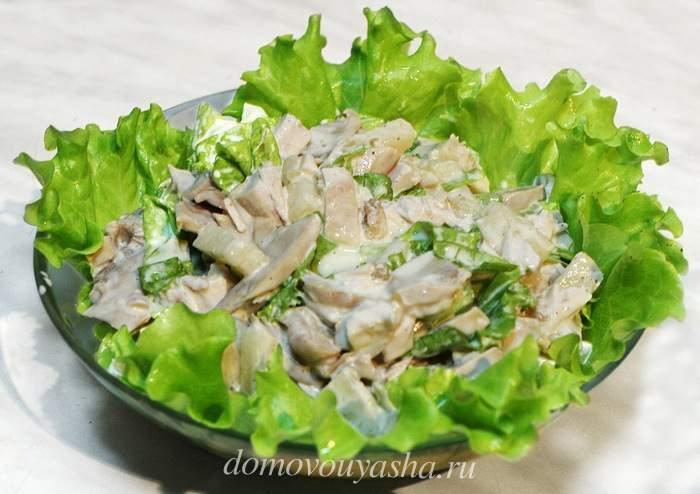 Салат «Марсель» с грибами и курицей, выложенный на листья зелени салата